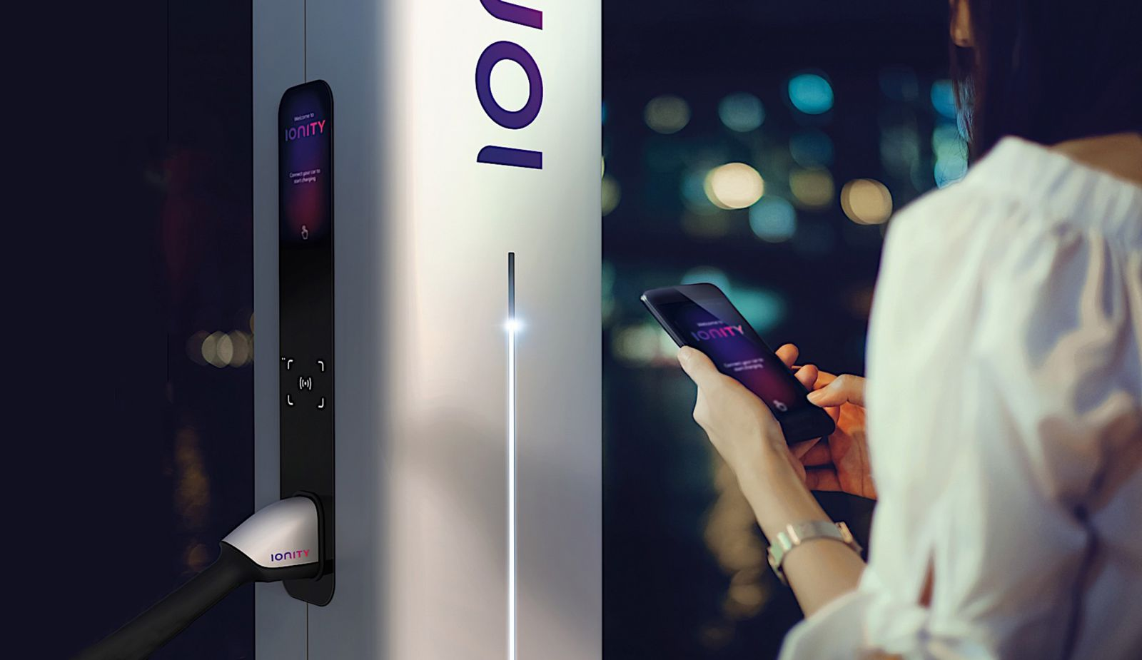 women standing in front of ionity charging station